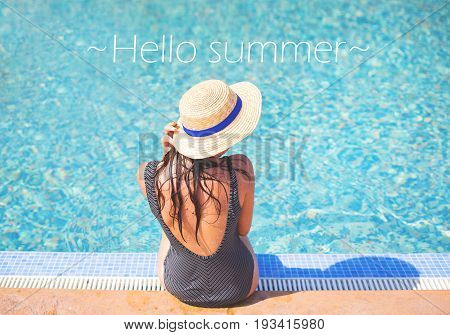 Beautiful girl in a swimsuit near the pool, inscription hi summer