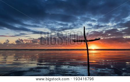 Cross on a beach at sunset with a reflection.