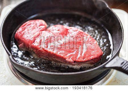 Raw angus steak fried on vegetable oil, iron cast