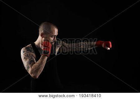 Profile studio shot of young professional boxer wearing black t-shirt and red gloves punching air in front of him while training preparing for boxing match showing different movements and strikes
