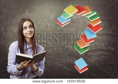 Portrait of a smiling young teen girl in a blue shirt holding an open book and standing near a blackboard with a question mark made of book. Toned image