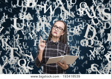 Portrait of a nerdy girl in glasses standing near a dark blue wall with white letters on it. Mock up