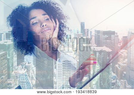 Portrait of a young African American woman sitting at a table and looking at her laptop screen. She is working. Typing with one hand and looking bored. City. Toned image double exposure