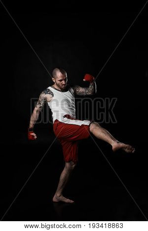 Confident muscular strong man wearing white A-shirt and boxing shorts practicing tae-bo exercises kicking forward with leg. Kickboxer or fighter showing his skills in studio on black background