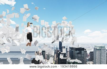 Portrait of a blond businesswoman standing on a skyscraper roof with binoculars and looking at a city around her. There are papers flying around. Mock up