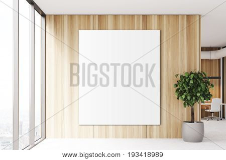 Blank vertical poster is hanging on a wooden wall of an office lobby. There is a panoramic window and a tree in a pot. 3d rendering mock up
