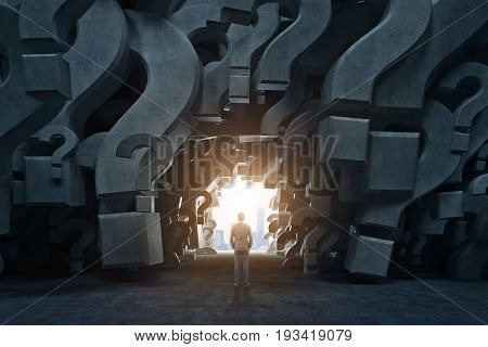 Rear view of a businessman standing in an empty room with gray 3d question marks on the walls. There is a way out near him. Close up. Concept of an answer search. 3d rendering mock up