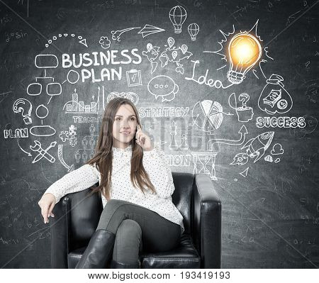 Young businesswoman with fair hair smiling and sitting in a leather armchair and talking on her smartphone. Blackboard with a business plan idea sketch