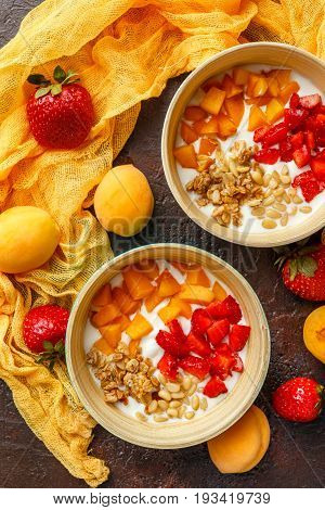 Natural yoghurt with pieces of apricots strawberries granola and pine nuts in two bowls on dark broun background. Top view