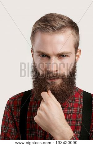 People and lifestyle. Fashion and style. Headshot of handsome young European macho man wearing treny clothing looking at camera deep in thoughts touching his fuzzy beard and squinting eyes