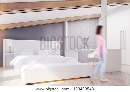 Woman in a gray attic bedroom with a wooden floor two large windows a white bed and a white table with a computer. Side view. 3d rendering mock up toned image