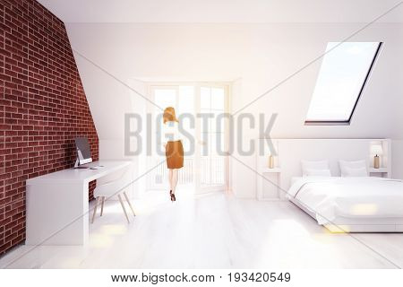 Woman in a brick attic bedroom with a white wooden floor a narrow window a white bed and a white table with a computer. 3d rendering mock up toned image