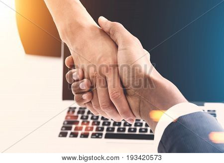 Close up of an African American man and a woman shaking hands. Office background. Concept of business partnership. Toned image.