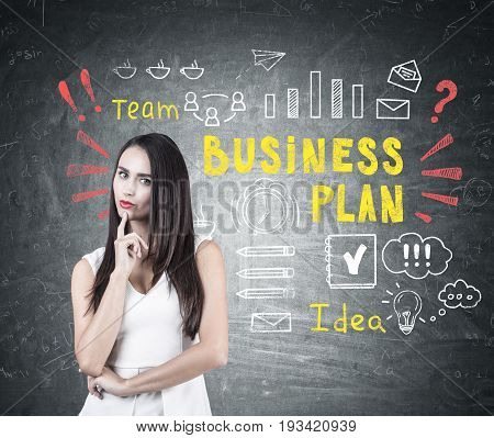 Portrait of a pensive businesswoman with dark hair. She is wearing a white shirt and standing near a blackboard with a colorful business plan sketch.