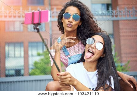 Carefree Girlfriends Making Face And Taking Selfies Outside