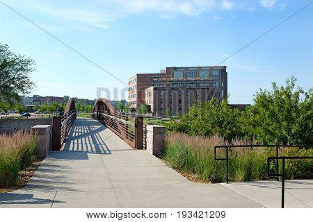 SIOUX FALLS, SOUTH DAKOTA - JUNE 21, 2017: Riverwalk footbridge along the Big Sioux River. Parks, hotels, restaurants and footbridges, line the popular area along the cities revitalized downtown.