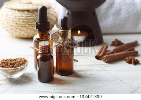 Composition with bottles of cinnamon oil on wooden background
