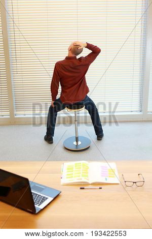middle age man relaxing neck - short break for exercise on pneumatic stool in office