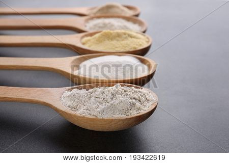 Wooden spoons with different types of flour on gray background