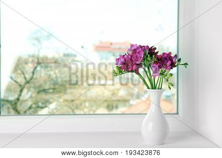 Vase with beautiful bouquet of freesia on windowsill