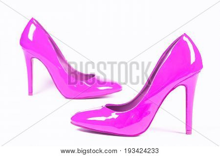 Sexy pink lacquered shoes high heels are on white background.