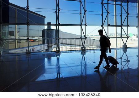 Traveler man walking with luggage in the airport