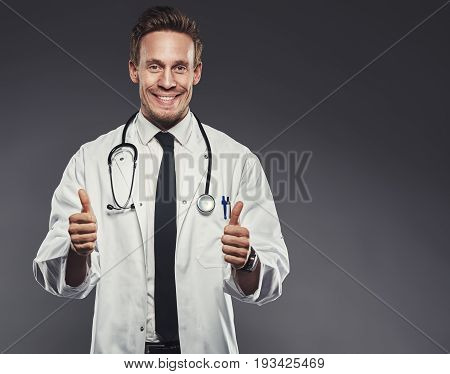Enthusiastic Doctor Giving The Thumbs Up Against A Grey Background