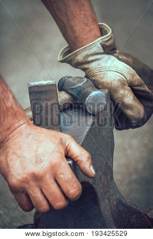 A blacksmith resting his hands on anvil after work at medieval fair festival in Streatham Park in London