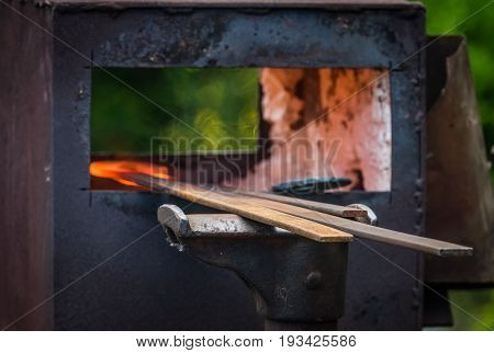 A blacksmith inserting steel rods into the hot oven  during medieval fair festival in Streatham Park in London