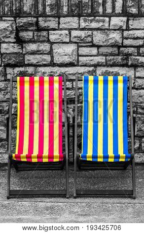 Empty red, blue and yellow striped deckchairs, Bournemouth, England