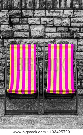 Empty purple and yellow striped deckchairs, Bournemouth, England