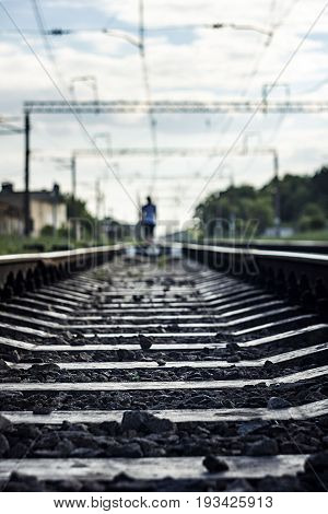 Silhouette Of A Man Walking On Rails Of A Train