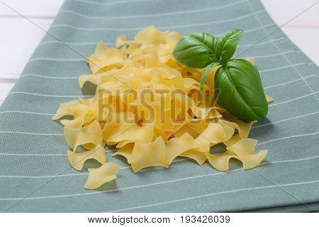 pile of quadretti - square shaped pasta on grey place mat - close up