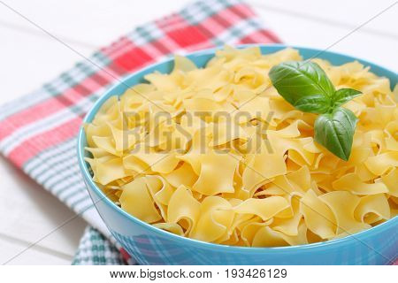 bowl of quadretti - square shaped pasta on checkered place mat - close up