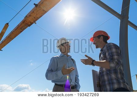 Builder And Business Man Discussing Project Meeting Outdoors On Buiding Constuction Site Two Engineer Talking