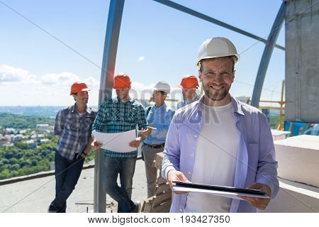 Team Of Builders On Site, Contractor Hold Plan Happy Smiling Over Apprentices Group Discussing Blueprint Engineers Teamwork Concept