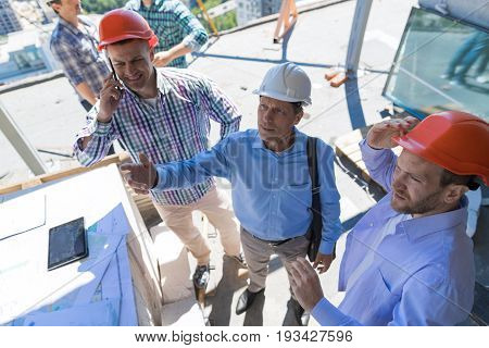 Builders On Construction Site With Contractor Reviewing Buiding Project, Team Meeting With Architect