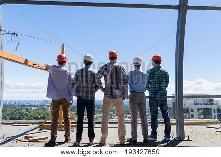 Team Of Builders On Costruction Site Back Rear View, Foreman Group In Hardhat Outdoors Teamwork Concept