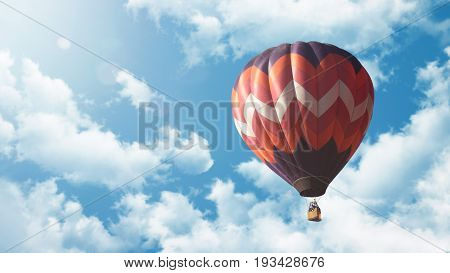 Colorful hot air balloon in front of blue sky with clouds and sunshine