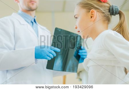Caucasian Girl Being Examined by Professional Medical Doctor. Reviewing X Ray Imagery.