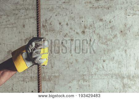 Concrete Reinforcement Concept Photo. Reinforcement Rod in a Hand of Construction Worker.