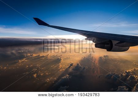 Beautiful sunset time with airplane wing seen through window of airplane.