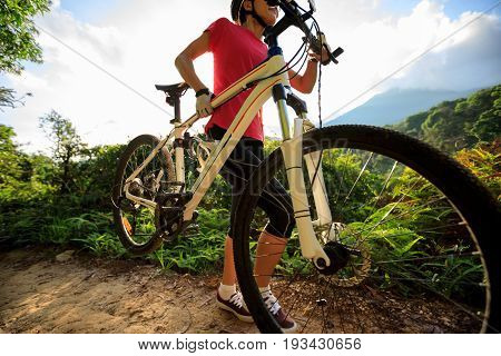 woman cyclist carrying mountain bike climbing on summer forest trail