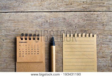 February. Calendar sheet. Two thousand seventeen year calendar pen and list of paper on wooden background.