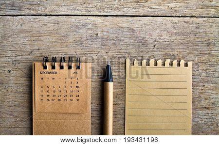 December. Calendar sheet. Two thousand seventeen year calendar pen and list of paper on wooden background.