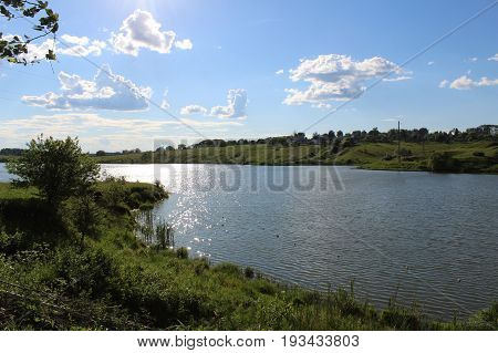 The lake is in good sunny weather. The water is riddled with a slight ripple. The shores of the lake are covered with luscious green vegetation.