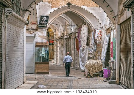 YAZD, IRAN - MAY 5, 2015: A man passes bazaars empty street in the old part of the city during afternoon break.