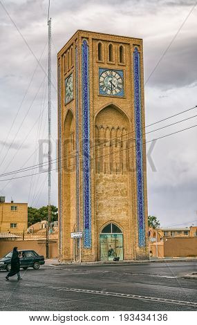 YAZD, IRAN - MAY 5, 2015: A woman wearing traditional clothes passes clock tower at Hazrat Mahdi avenue in the old part of the city.