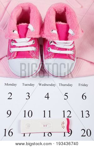 Pregnancy Test With Positive Result And Clothing For Baby On Calendar