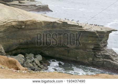 Sheer cliffs falling as result of erosion by ocean